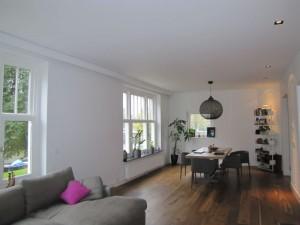 De woonkamer met zithoek en grote tafel