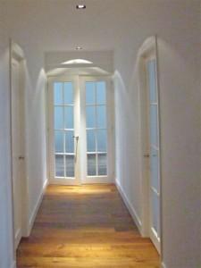 De hal met in het plafond ingebouwde spots voor een fraai lichtspel. De nieuwe kozijnen en deuren behouden het 30er-jaren uiterlijk van het appartement