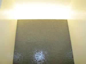Indirecte verlichting boven in de betegelde achterwand van het toilet