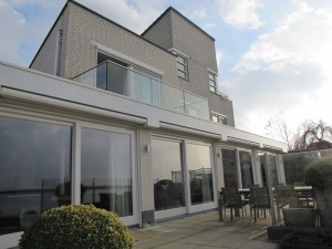 Het nieuwe balkonhek op de eerste verdieping, met glas en RVS.