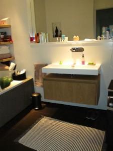 Het badkamer meubel is maatwerk, uitgevoerd met greeploze lade en gefineerd met licht eiken.